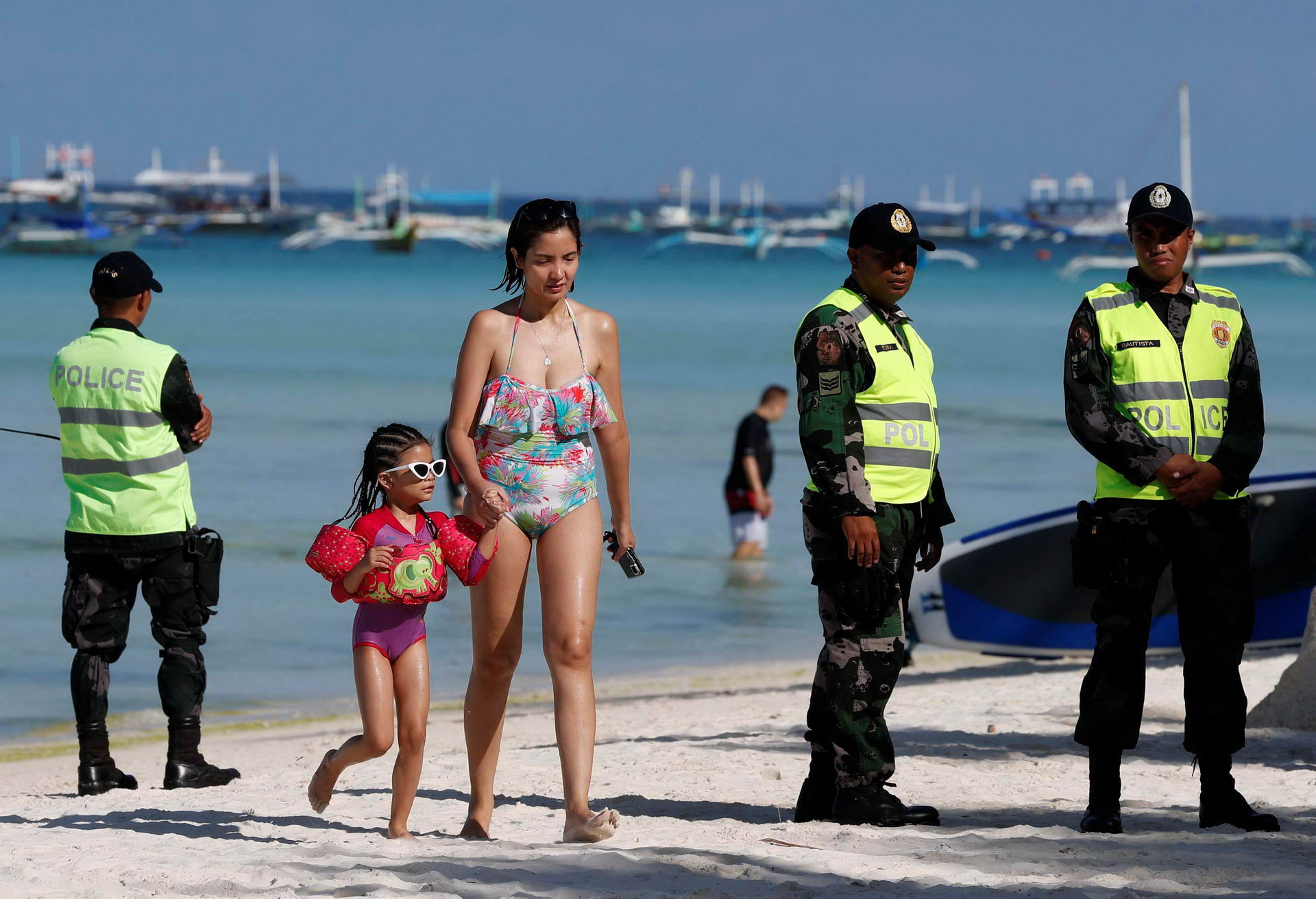 Tourists walk past policemen, one day before the temporary closure of the holiday island Boracay, in the Philippines