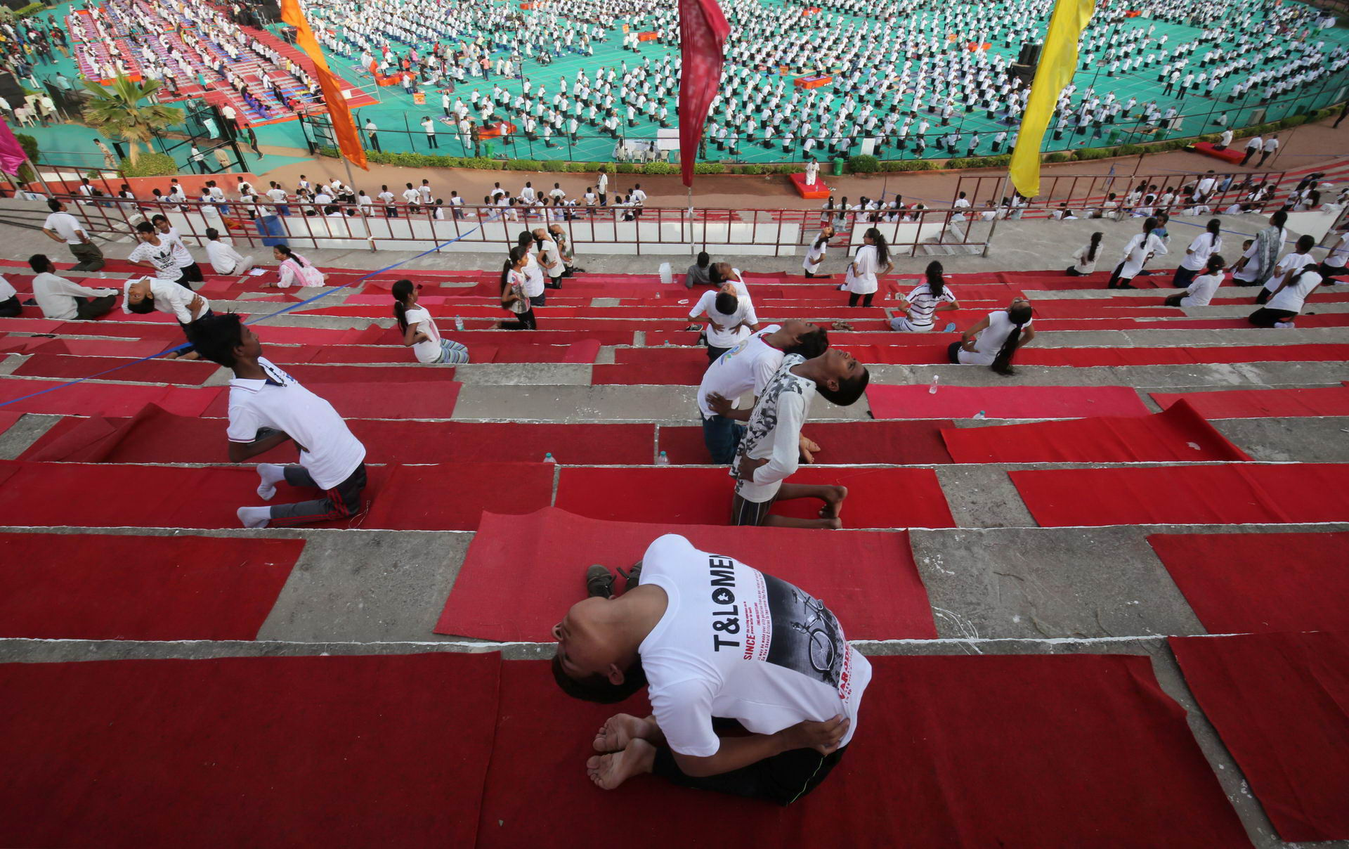 Participants perform yoga at a stadium during International Yoga Day in Ahmedabad