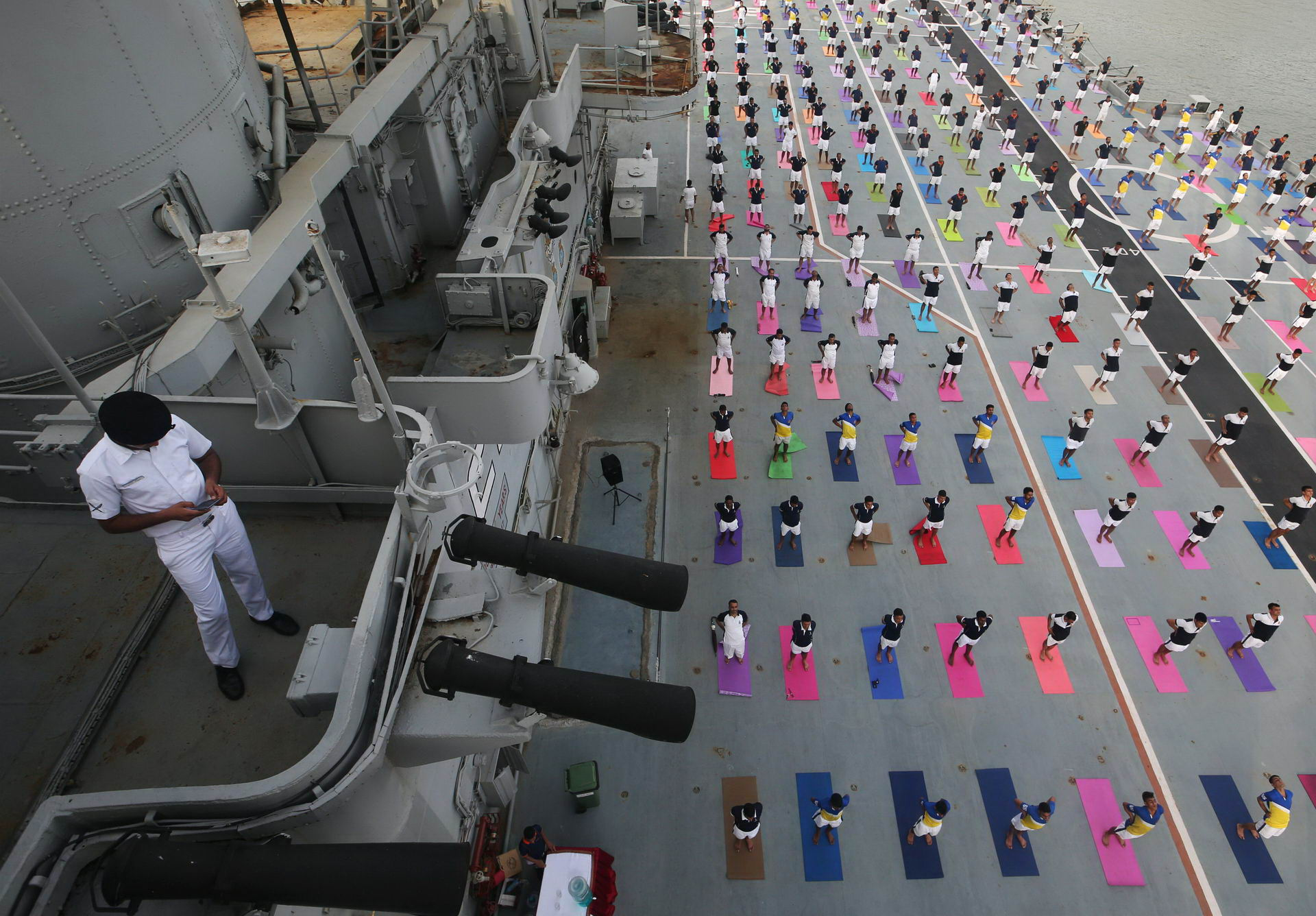 Members of Indian Navy perform yoga on the flight deck of INS Viraat, an Indian Navy's decommissioned aircraft carrier, during International Yoga Day in Mumbai