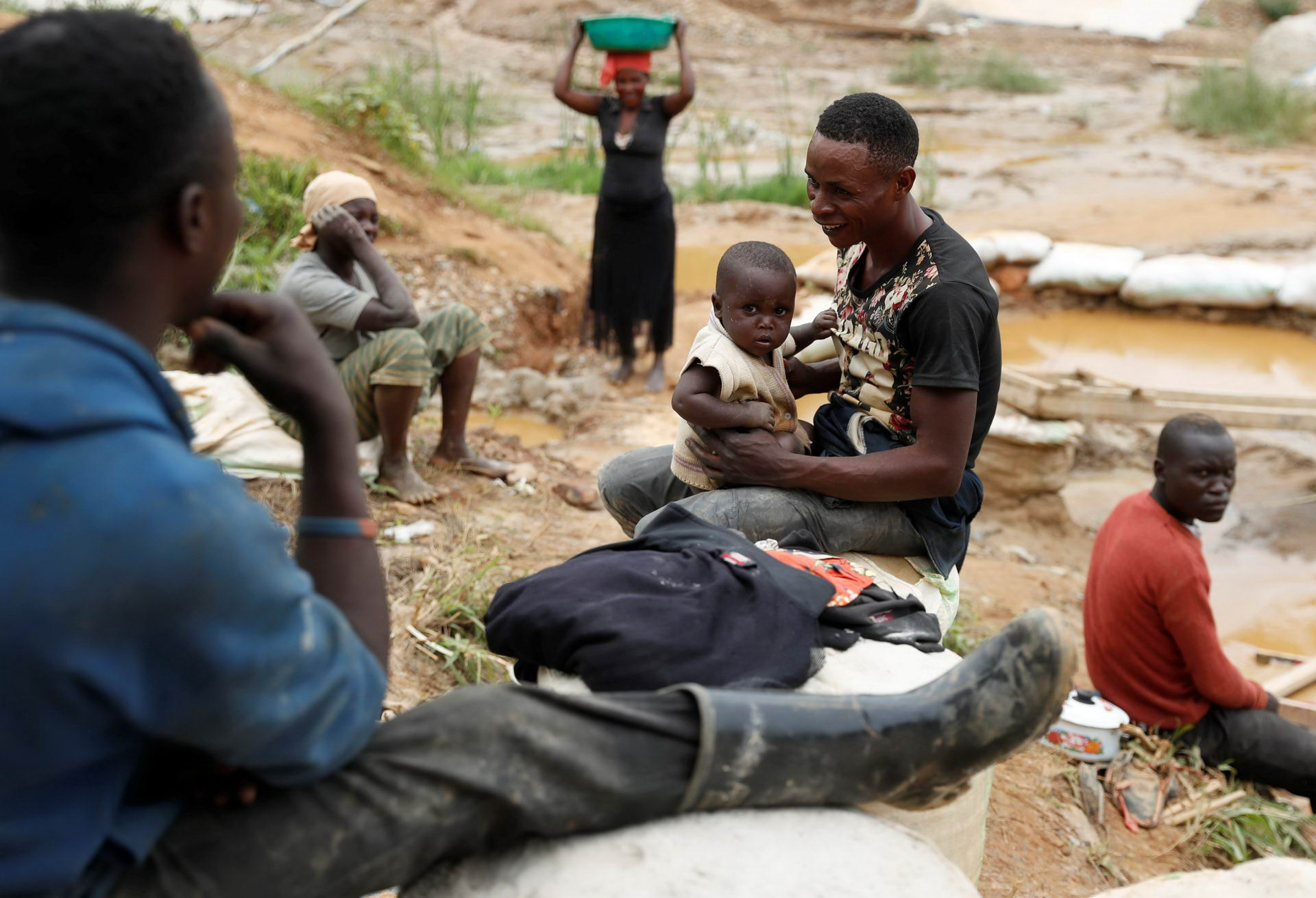 A man plays with his son at Makala gold mine camp near the town of Mongbwalu in Ituri province