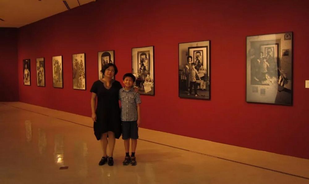 Художница 17 лет фотографируется с сыном, делая снимки на фоне предыдущих