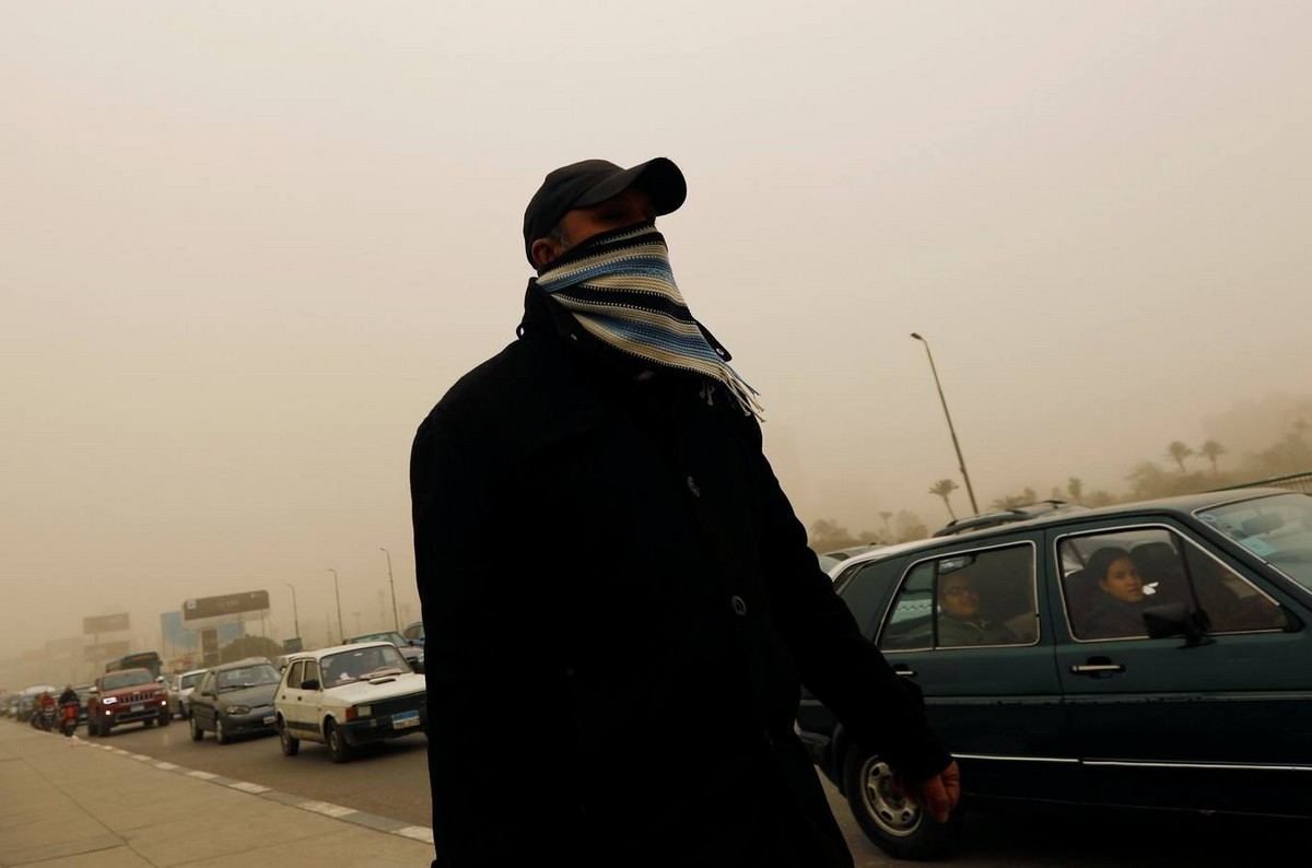 A man covers his face during a sandstorm in Cairo