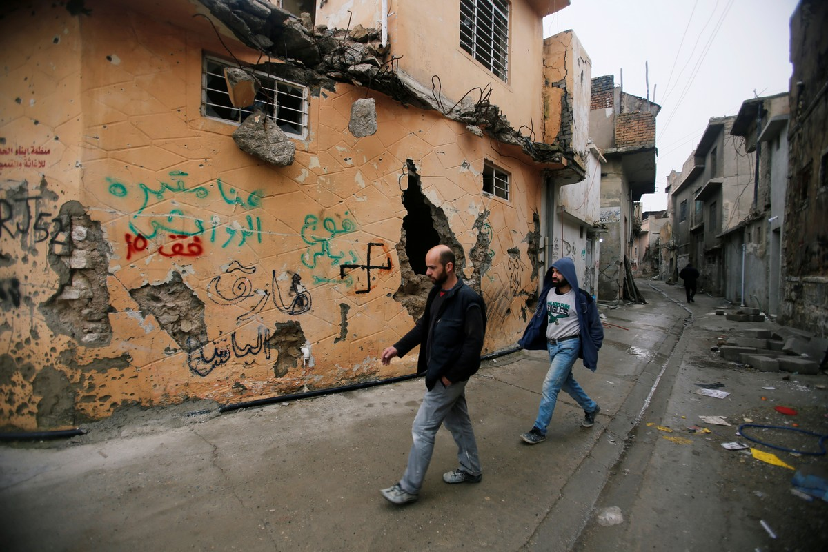 Iraqi men walk on a street of the Old City of Mosul