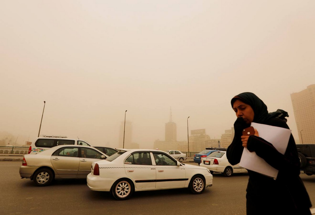 A woman covers her face as she walks on the 6th October Bridge during a sandstorm in Cairo