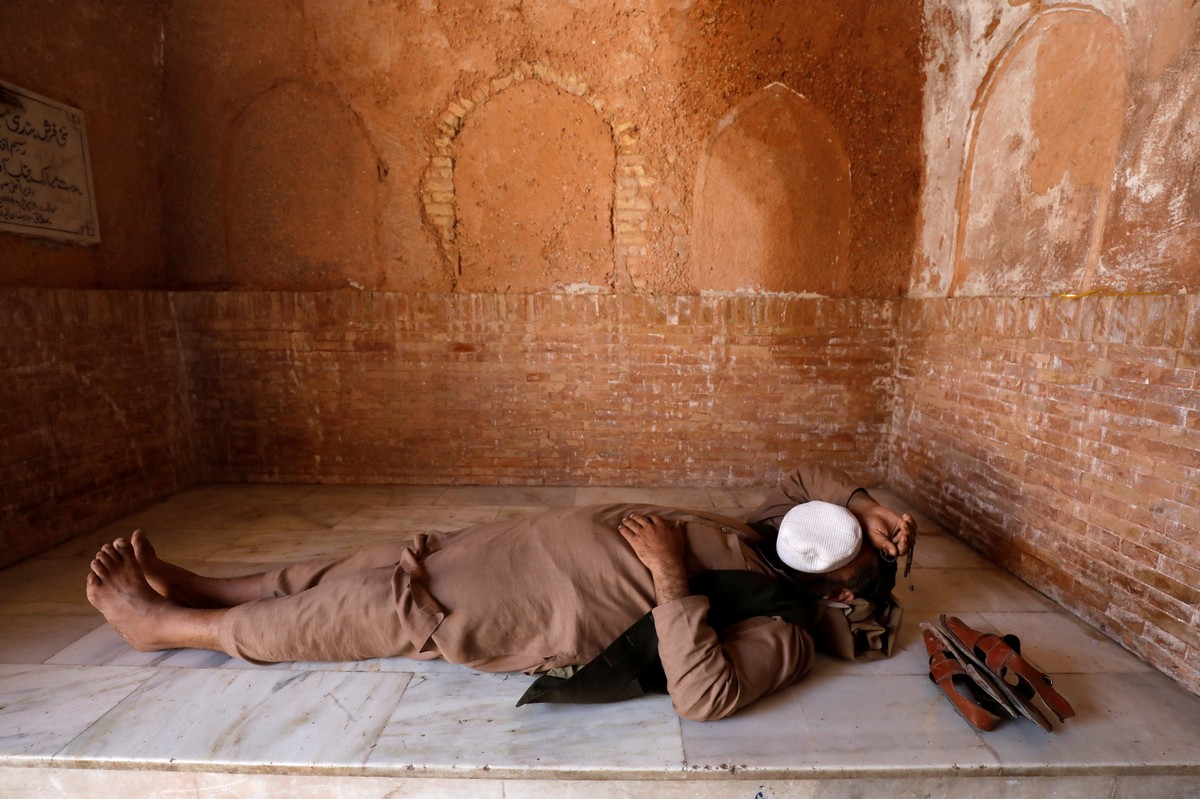 A man with a cap on his face sleeps on a floor at the Mahabat Khan Mosque in Peshawar
