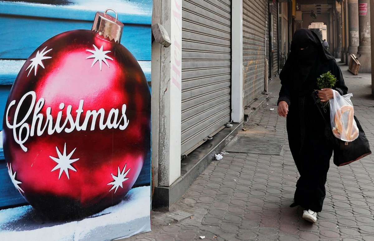 An Egyptian woman wearing a full veil (niqab) walks in front of a Christmas decorations shop in Cairo