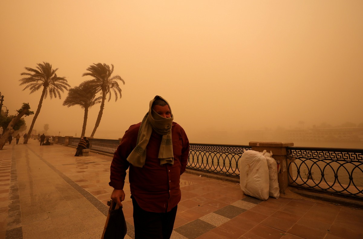 A man covers his face during a sandstorm near the River Nile in Cairo