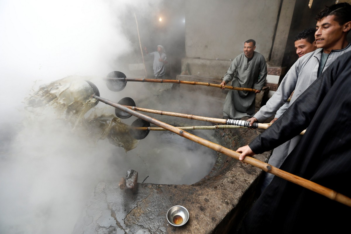 "Workers cook ""black honey"" molasses, made from sugar cane at a small factory in Mallawi"